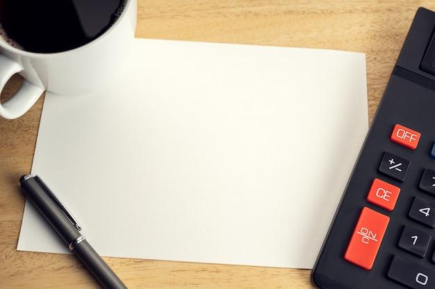 Leeres papier auf hölzernem schreibtisch tisch mit tasse kaffee und taschenrechner. mock-up-vorlage. wirtschafts-, finanz- oder geschäftskonzept