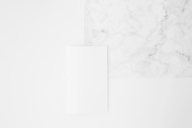 Leeres papier auf marmorbeschaffenheit gegen weißen hintergrund