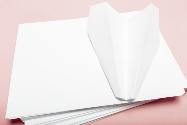 Leeres papier auf rosa pastellschreibtisch