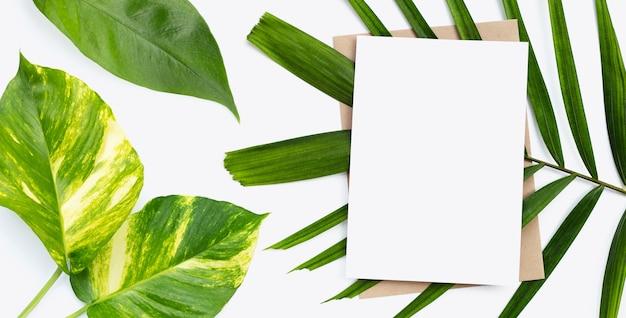Leeres papier auf tropischem blatthintergrund. platz kopieren