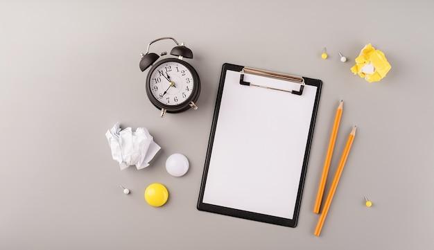 Leeres papier auf weißem wecker der zwischenablage und draufsicht auf briefpapier auf grauem hintergrund