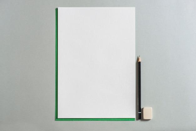 Leeres papier, bleistift und radiergummi auf grauem hintergrund