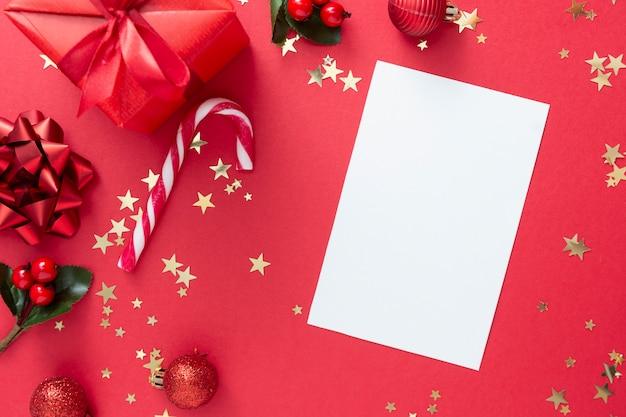 Leeres papier der weihnachtsgrußkarte, rote geschenkbox auf rotem hintergrund und goldene funkelnde konfettis, zuckerstange.