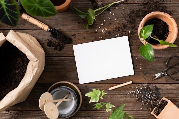 Leeres papier im gartenarbeitshintergrund der zimmerpflanze