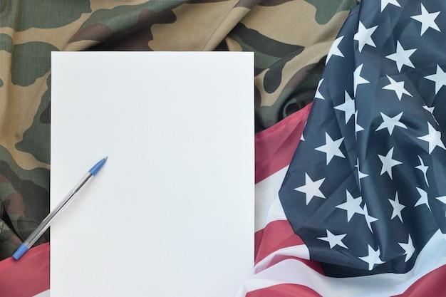 Leeres papier liegt auf der flagge der vereinigten staaten von amerika und der gefalteten militäruniformjacke. militärische symbole.