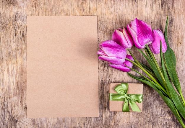 Leeres papier mit geschenkbox und tulpen