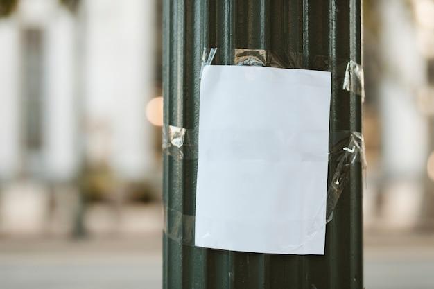 Leeres papier mit klebeband auf einer grünen säule