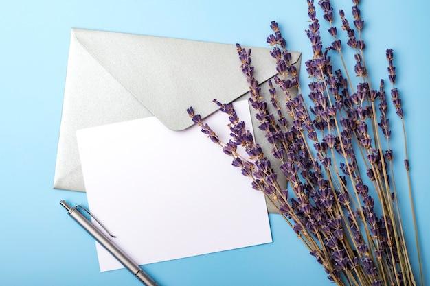 Leeres papier mit umschlag und lavendelblumen auf einem blauen hintergrund. einfache hochzeitskarte. sicht von oben