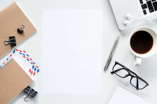 Leeres papier mitten in weißem schreibtisch in der ebenenlage.