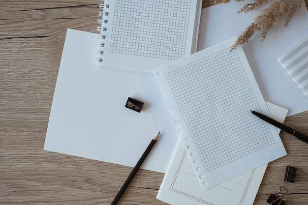 Leeres papierblatt auf dem tisch. künstler-home-office-schreibtisch-arbeitsplatz mit bleistift, pampasgras