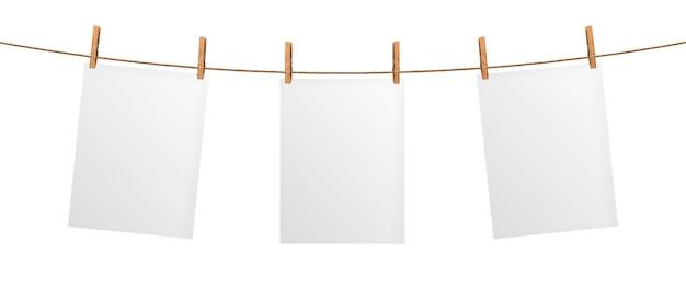 Leeres papierblatt, das am seil, lokalisiert auf weißem hintergrund hängt