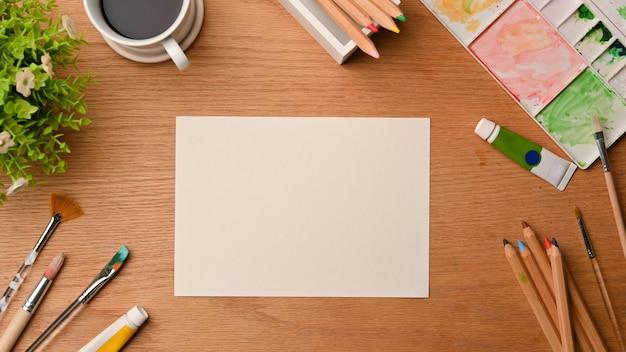 Leeres papierblatt des kreativen kunstarbeitsplatzes umgeben von malwerkzeugen auf draufsicht des hölzernen hintergrundes