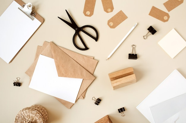 Leeres papierblatt mit umschlag auf beigem tisch. künstler home office schreibtisch arbeitsbereich mit holzschatulle, bleistift und briefpapier