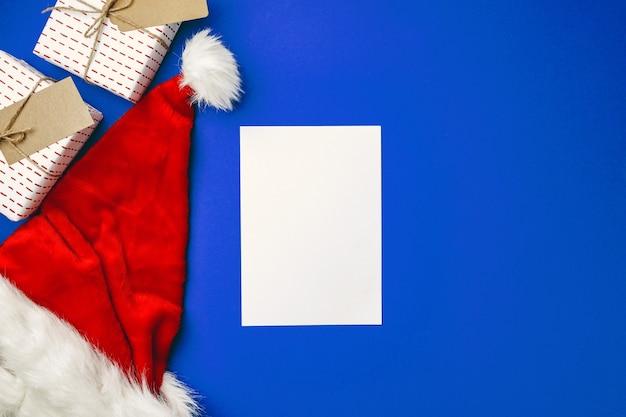 Leeres papierblatt und snata claus-hut auf blauer, flacher lage, draufsicht