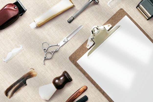 Leeres papierklemmbrett flach mit friseurwerkzeug-job- und karrierekonzept