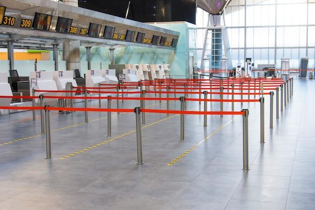Leeres passagierterminal am flughafen. die wege sind begrenzt und durch einen roten flug zum check-in-schalter getrennt.