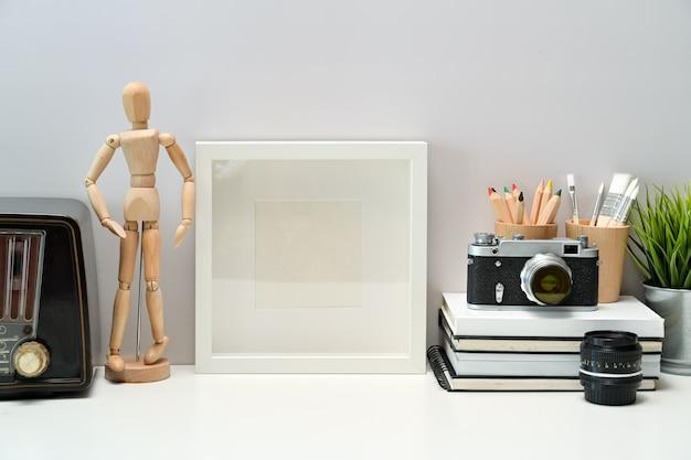 Leeres plakat des modells, bücher, weinleseradio und weinlesekamera auf arbeitsplatzschreibtisch
