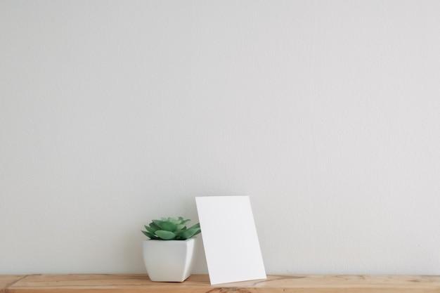 Leeres postkartenmodell mit kaktustopf auf weißer wand