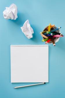 Leeres quadratisches notizbuch, buntstifte und zerknitterte papiere. leeres blatt.