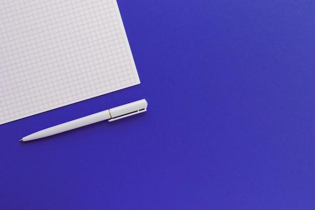 Leeres quadratisches papier und stift auf trendigem blauem hintergrund. für ideen nachricht, liste und inspiration. draufsicht, flach liegen mit kopierraum. modell für ihr design.