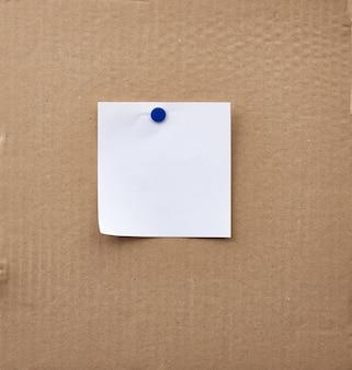 Leeres quadratisches weißes blatt papier, das mit einem eisenknopf befestigt ist