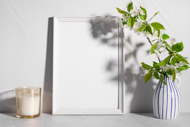 Leeres rahmenmodell mit baumblüten in vase und duftkerze