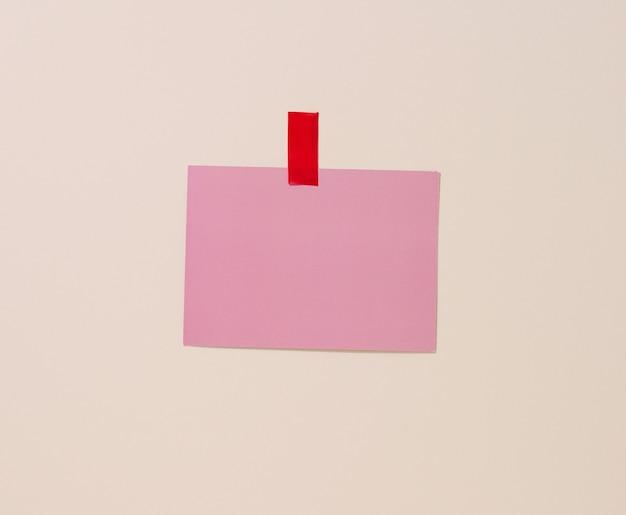 Leeres rechteckiges rosa blatt papier auf einem hellblauen hintergrund geklebt. platz für eine inschrift, ankündigung