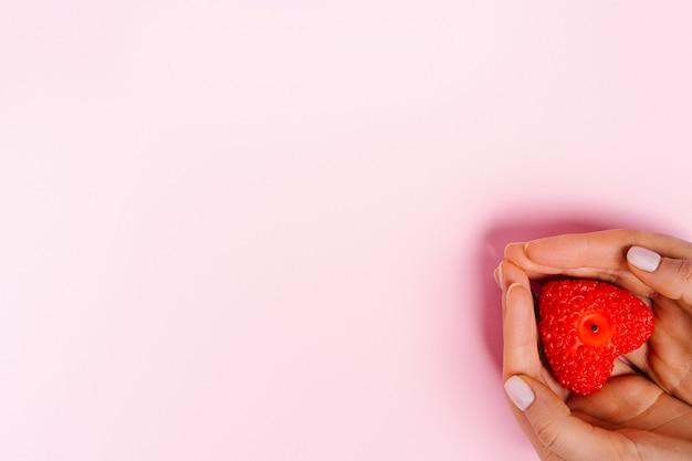 Leeres rosa banner für werbung in der ecke der weiblichen hände mit einer roten kerze mit herzform.