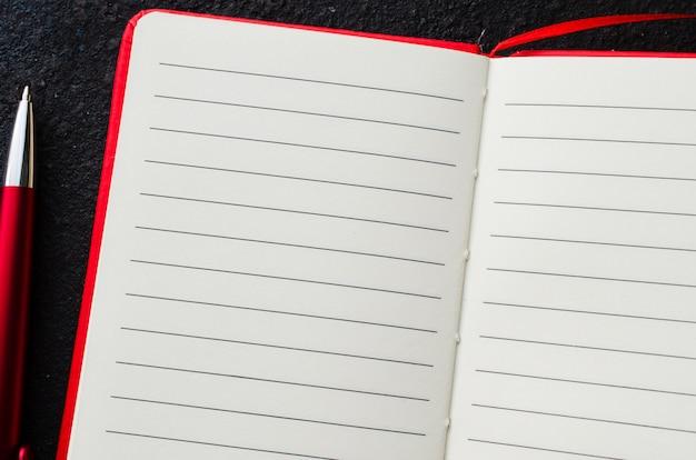 Leeres rotes notizbuch mit rotem stift auf dunklem hintergrund