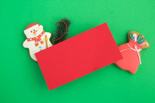 Leeres rotes papier für weihnachtsgrüße und lebkuchen auf dem grünen hintergrund