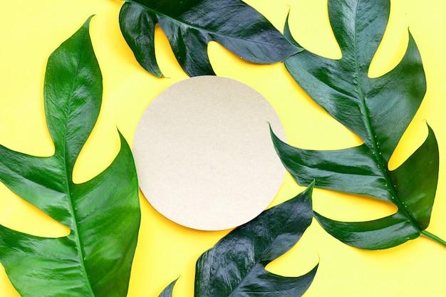 Leeres rundes braunes papier auf monstera deliciosa liebm-blättern auf gelbem hintergrund.
