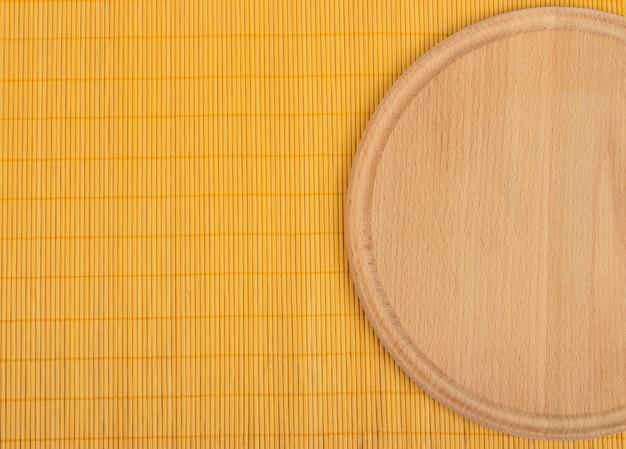 Leeres rundes hölzernes brett mit tischdeckenhintergrund