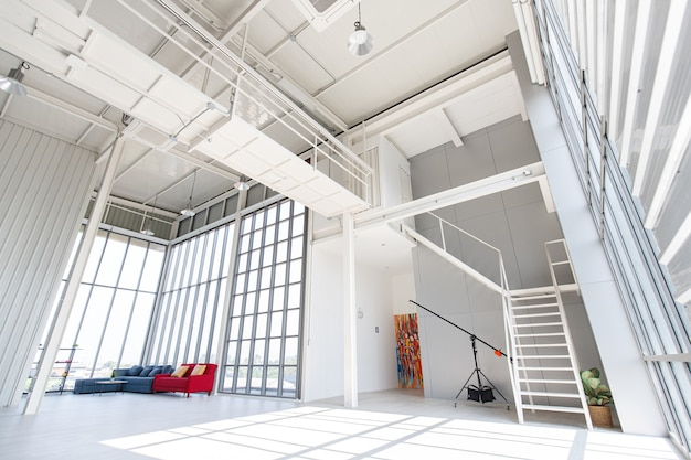Leeres, sauberes, zweistöckiges innen-innenraum-industrie-loft-design-fotografie-studio-workshop-wohnzimmer in einer wohnung voller platz mit sofagarnitur mit kunsttreppen-glühbirnen-klimaanlage.