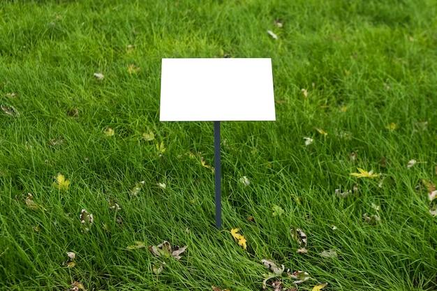 Leeres schild auf gras. immobilienhaus zum verkauf schild