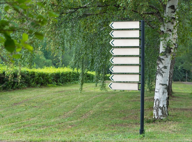 Leeres schild im park auf einem hintergrund von bäumen