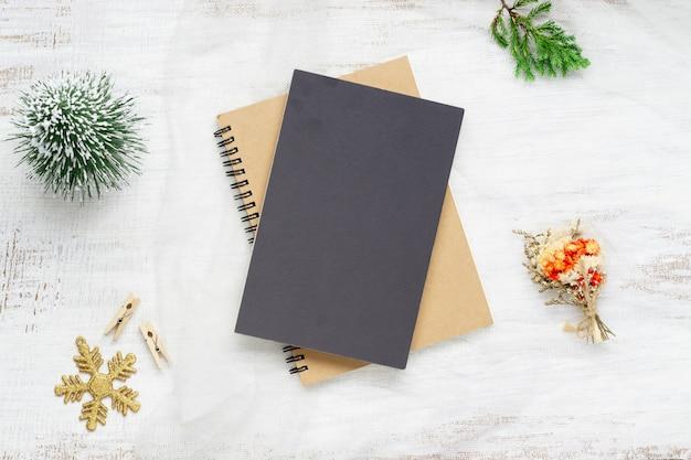 Leeres schwarzes abdeckungsnotizbuch und weihnachtsverzierungen auf weißem holz
