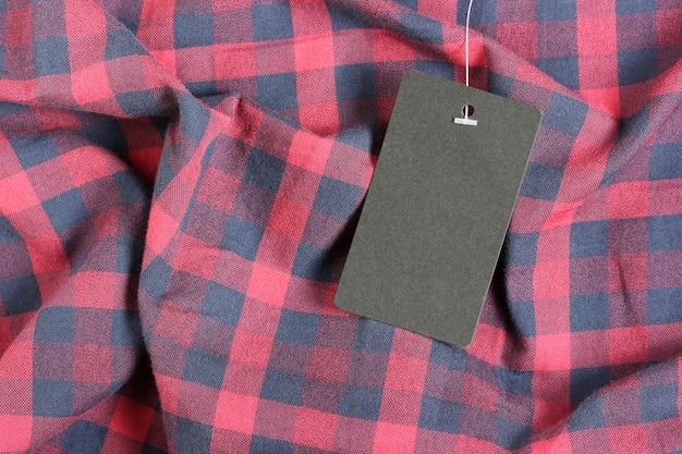 Leeres schwarzes etikett auf rot kariertem stoff, draufsicht