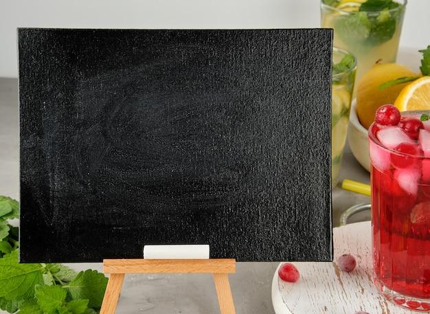 Leeres schwarzes kreidebrett für das schreiben eines sommergetränkrezepts und eines glases mit beerenlimonade