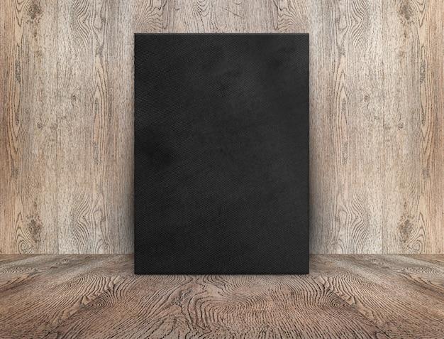Leeres schwarzes leinwandplakat, das an holzwand auf holzboden im perspektivischen raum lehnt