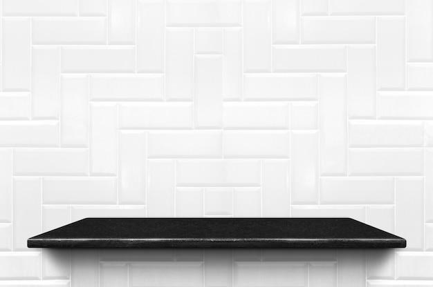 Leeres schwarzes marmorregal am weißen keramikfliesenwandmusterhintergrund