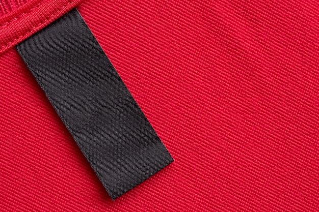 Leeres schwarzes wäschepflege-kleidungsetikett auf rotem stoffbeschaffenheitshintergrund