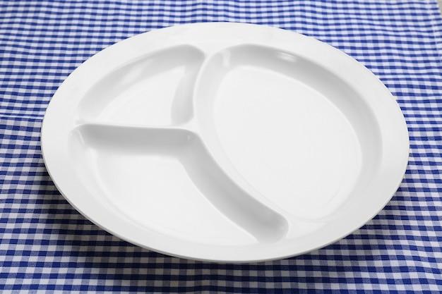 Leeres serviertablett für lebensmittel auf tischdecke