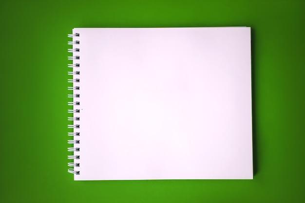 Leeres skizzenbuch auf grünem hintergrund, freier speicherplatz. draufsicht auf leeren notizblock im rustikalen stil, kopienraum für text oder werbung.