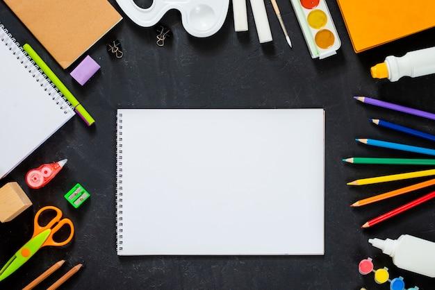 Leeres skizzenbuch mit schulmaterial auf tafelhintergrund. zurück zum schulkonzept. rahmen, flatlat, kopierraum für text. attrappe, lehrmodell, simulation