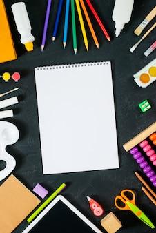 Leeres skizzenbuch mit schulmaterial auf tafelhintergrund. zurück zum schulkonzept. rahmen, flatlay, kopierraum für text. attrappe, lehrmodell, simulation