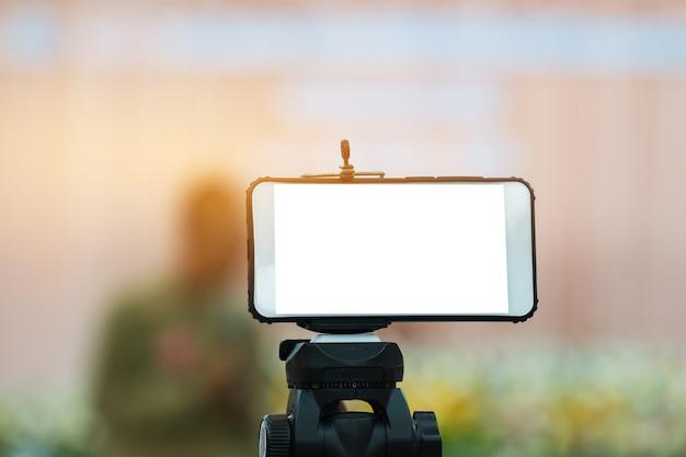Leeres smartphone des lcd-bildschirms auf stativ für kopienraum in ihrer textnachricht
