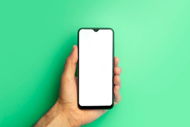 Leeres smartphone in der hand auf farbigem blauem banner-hintergrundmodell mit leerem bildschirm auf minimalem...