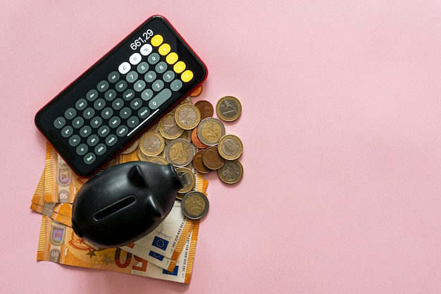 Leeres sparschwein mit der menge an ersparnissen daneben über einem rosa tisch. geld sparen konzept