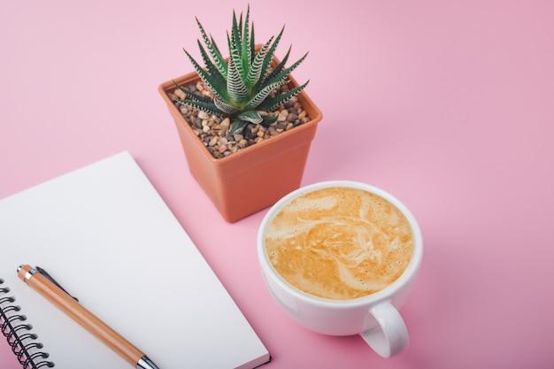 Leeres spiralheft auf rosa hintergrund und tasse lattekaffee