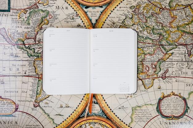 Leeres tagebuch des reisenden auf historischer karte